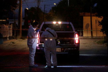 Forensic technicians work at a crime scene where three men were killed by unknown assailants in the municipality of Cadereyta Jimenez