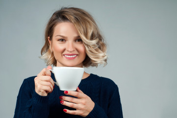 Woman in warm sweater is holding a cup of coffee.