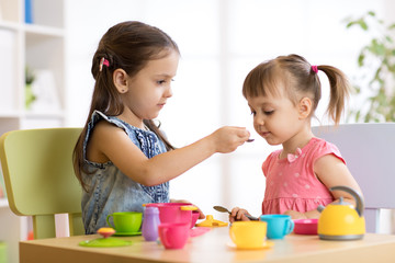 Cute little children playing with kitchenware while sitting at table at home or kindergarten