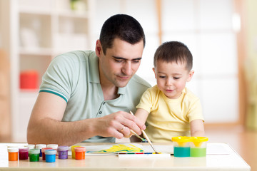 Father and son are painting together. Happy family are coloring with paintbrush. Man and child have a fun pastime.