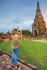 Young traveller taking smartphone photo with mobile phone at Wat Chaiwatthanaram temple in Ayutthaya.