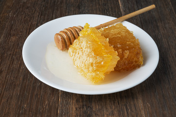 honeycomb and honey stick on a white plate