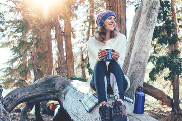 Traveling young woman with knitted hat drinking hot coffee from a mug and sitting on tree in wild forest at sunny day.