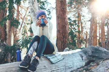 Traveling happy woman with knitted hat drinking hot coffee from a mug and sitting on tree in wild forest at sunny day.