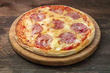 Pepperoni pizza on pizza stone and rustic texture, closeup photo