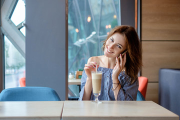 Cheerful young lady at the restaurant talking on the phone