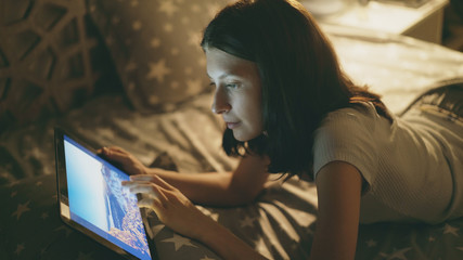 Young smiling woman lying on bed watching photographs from travel on digital tablet computer at night at home