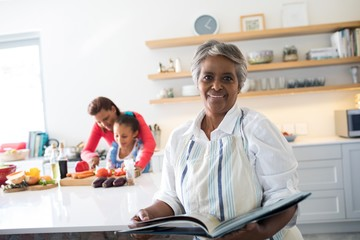 Portrait of smiling senior woman holding recipe book in kitchen