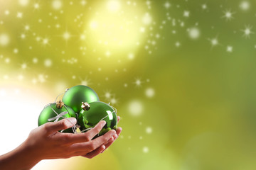 hands with balls and christmas ornaments