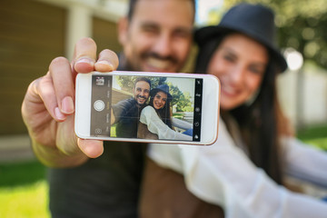 Smiling young couple take a selfie at city park.