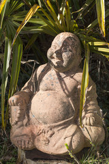 Statue of Budda in a garden.