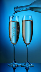 The aromatic champagne from the bottle is poured into two glasse