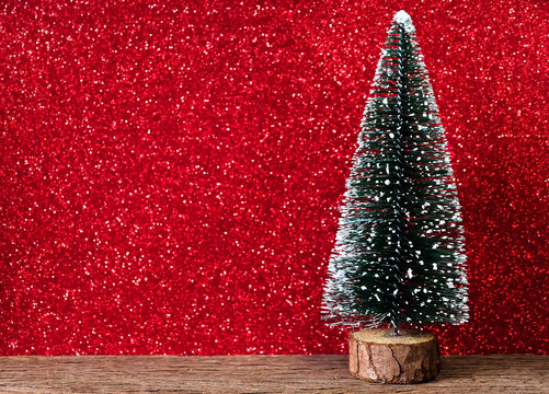 christmas tree on wood table with red glitter background