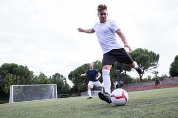 Soccer player kicking a ball during a soccer match