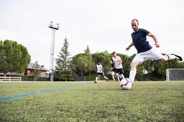 Concentrated man playing football game with other players and kicking ball.