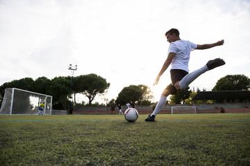 Man in sports uniform kicking ball during football match on big football field.