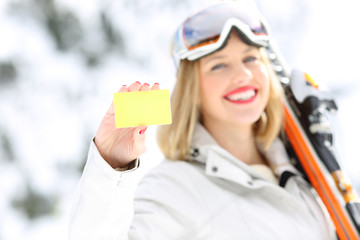 Happy skier showing a card in a slope