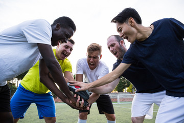 Confident screaming men in sportswoman of soccer players stacking hands together in support and shouting.