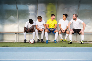 Football players sitting on bench and having nice chat before match.