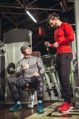 Young man and his personal fitness trainer in the gym exercising