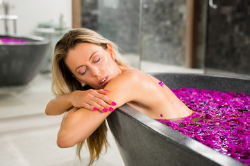 Woman relaxing in violet flowers bathtub