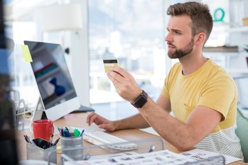 Male executive doing online shopping on computer at desk