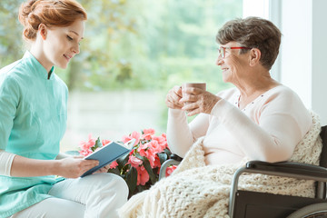 Assistant reads book for elderly