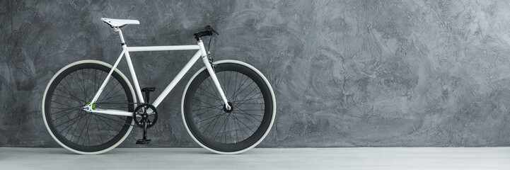 White bicycle against concrete wall