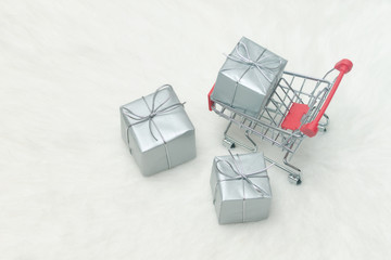Shopping cart with gift boxes on white background. Holiday sale