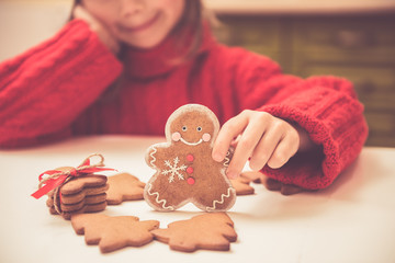 Beautiful girl child plays with ginger cookies. Christmas, celebration, cooking concepts