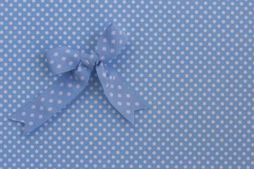 Blue ribbon on polka dots.