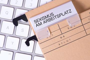 Ein Computer und Ordner mit dem Aufdruck Sexismus am Arbeitsplatz