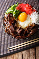 Japanese cuisine: gyudon beef with rice and onion. Vertical top view