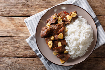Philippine food: Salpicao beef with garlic and rice closeup on a plate. Horizontal top view