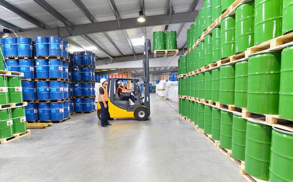 Arbeiter in einem Warenlager für Chemiekalien lagern Fässer // Workers in logistics
