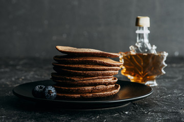 stacked chocolate pancakes with bottle of maple syrup