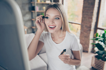 Attractive beautiful excited lovely cute cheerful smiling blonde is applying mascara  and looking in the mirror