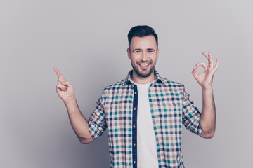 Portrait of attractive, cheerful brunet with stubble man in casual outfit showing ok sign, pointing at copy space, looking at camera over grey background Wall mural