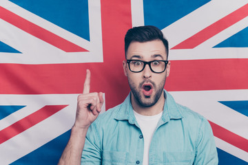 Portrait of handsome attractive guy with stubble in glasses showing index finger up, find a solution, have an idea with opened mouth over English flag background