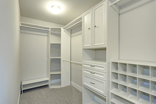 Narrow walk-in closet lined with built-in drawers