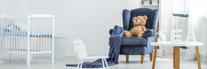Teddy bear sitting on armchair