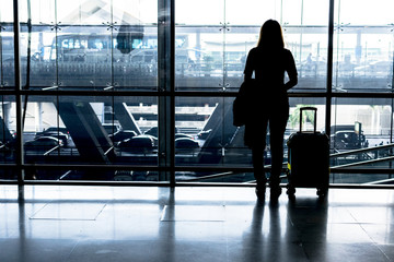 silhouette of girl with luggage stand near window in airport