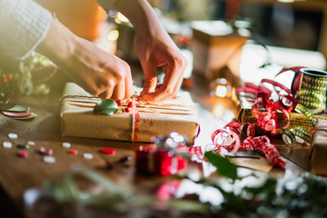 Christmas time. close-up on woman's hands wrapping a gift