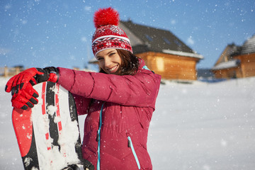 Winter woman with snowboard outdoors