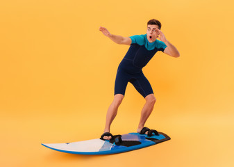 Image of Shocked surfer in wetsuit using surfboard
