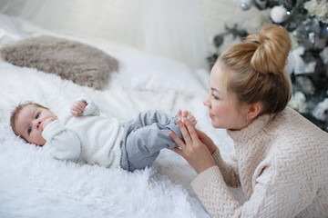 Happy young mother and her son playing at home during Christmas holidays.Christmas family portrait of a young beautiful woman with a newborn son.