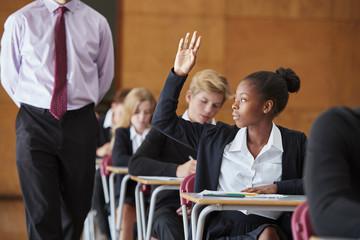 Teenage Student Sitting Examination Asking Teacher Question