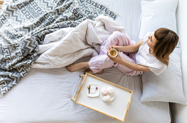 overhead view of woman with cup of coffee sitting on bed in morning