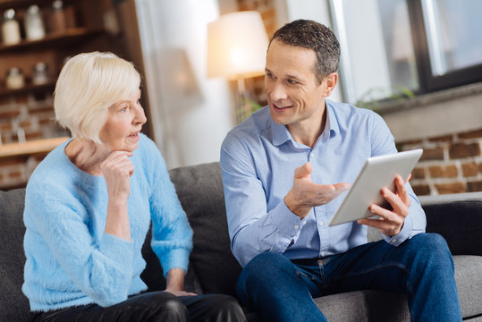Becoming tech-literate. Handsome young man sitting on the couch next to his elderly mother and explaining her how to use a tablet while she listening attentively