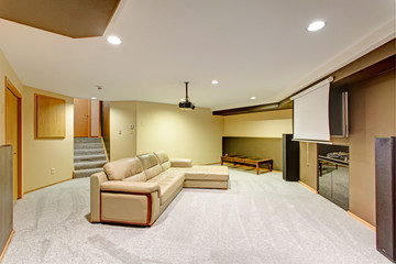 Beige basement movie room with a leather sectional